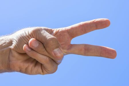 Foto de Closeup low angle of male hand showing peace sign with blue sky background on sunny day in natural light - Imagen libre de derechos