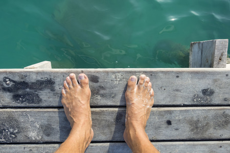 Foto de High angle POV of man's bare feet standing at edge of wooden dock sprinkled with fine white sand above aqua green sea water in natural morning light - Imagen libre de derechos