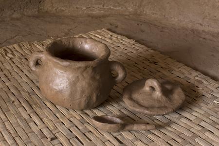 Foto de Primitive fresh thrown pottery consisting of bowl, lid and spoon sit drying on woven mat inside adobe hut with earthen floor - Imagen libre de derechos