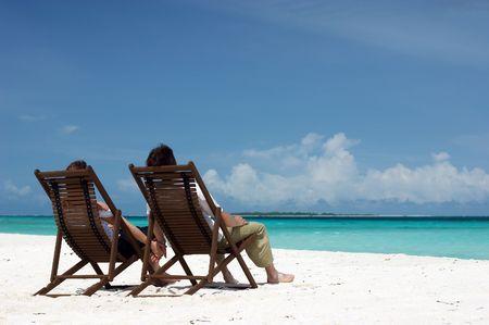Foto de Young couple sitting on the white sandy beach - Imagen libre de derechos