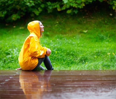 Happy young woman in yellow raincoat under rain