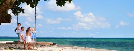 Foto de Family of four having fun on tropical beach - Imagen libre de derechos