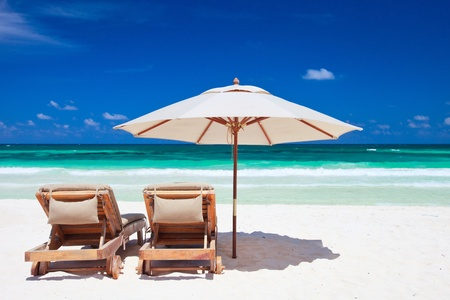 Two chairs and umbrella on stunning tropical beach in Tulum, Mexico
