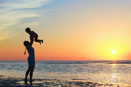 Photo for Mother and little daughter silhouettes on beach at sunset - Royalty Free Image