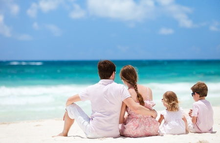 Photo pour Family of four sitting on Caribbean beach - image libre de droit