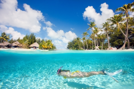 Foto de Woman swimming underwater in clear tropical waters in front of exotic island - Imagen libre de derechos