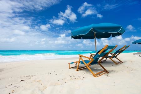 Foto de Chairs and umbrella on a beautiful tropical beach at Anguilla, Caribbean - Imagen libre de derechos