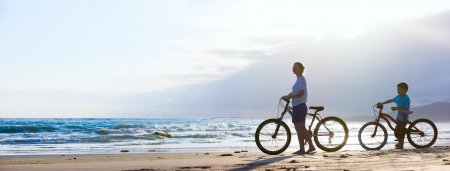 Photo for Panorama of mother and son biking on a beach at sunset - Royalty Free Image
