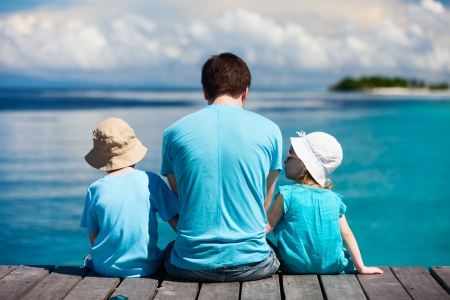 Photo for Back view of father and kids sitting on wooden dock looking to ocean  - Royalty Free Image