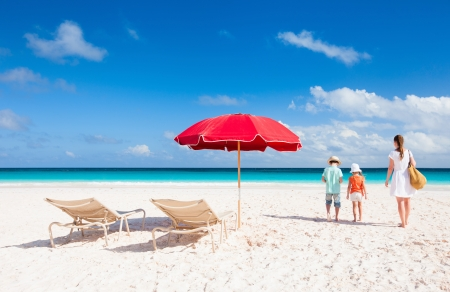 Foto de Two chairs under umbrella on a beautiful tropical beach with family walking nearby - Imagen libre de derechos