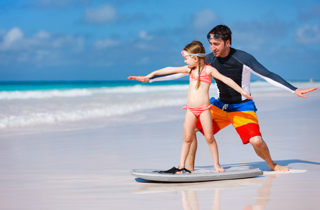 Photo for Father and daughter at beach practicing surfing position - Royalty Free Image