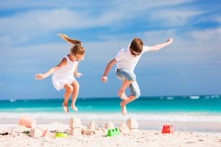 Photo for Two kids crushing sandcastle on summer vacation - Royalty Free Image