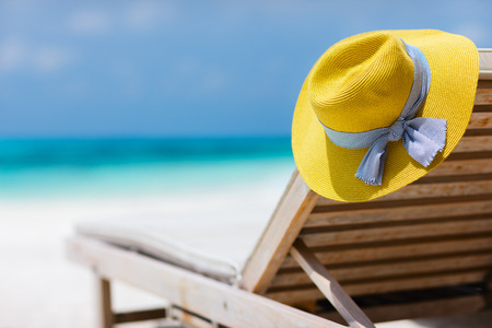Foto de Yellow hat on a lounge chair at tropical beach - Imagen libre de derechos
