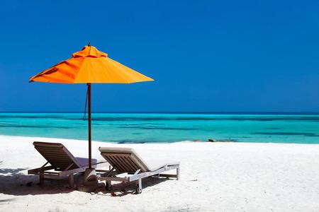 Foto de Chairs and orange umbrella on a beautiful tropical beach at Maldives - Imagen libre de derechos