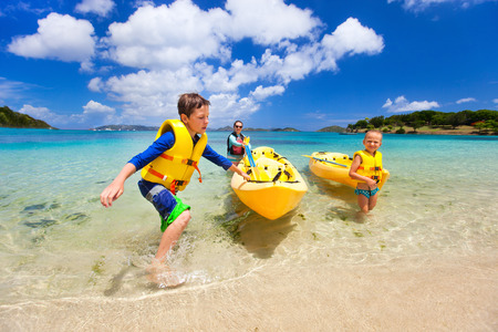 Photo pour Family with kids paddling on colorful yellow kayaks at tropical ocean water during summer vacation - image libre de droit