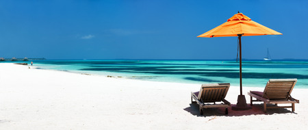 Photo pour Wooden lounge chairs and orange sun umbrella on a beautiful tropical beach at Maldives - image libre de droit