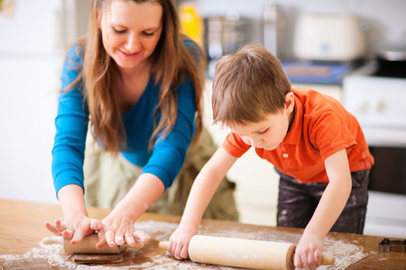 Photo pour Young mother and her little son baking cookies together at home kitchen - image libre de droit