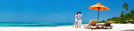 Foto de Romantic couple on a tropical beach during honeymoon vacation, wide panorama perfect for banners - Imagen libre de derechos