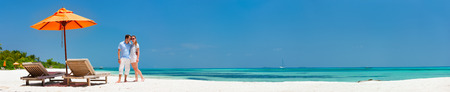 Foto de Romantic couple on a tropical beach during honeymoon vacation, super wide panorama perfect for banners - Imagen libre de derechos
