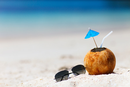 Foto de Tropical cocktail in a coconut on a beautiful beach - Imagen libre de derechos