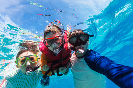 Photo pour Underwater portrait of family snorkeling together at clear tropical ocean - image libre de droit