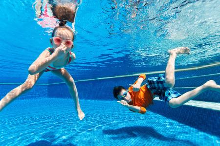 Foto de Kids having fun playing underwater in swimming pool on summer vacation - Imagen libre de derechos