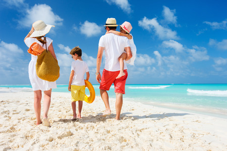 Photo pour Back view of a happy family at tropical beach on summer vacation - image libre de droit