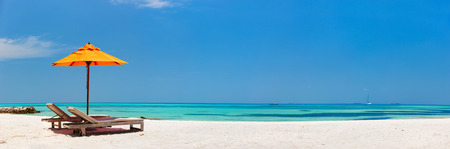 Foto de Wooden lounge chairs and orange sun umbrella on a beautiful tropical beach at Maldives - Imagen libre de derechos