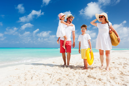 Foto de Happy beautiful family with kids walking together on tropical beach during summer vacation - Imagen libre de derechos