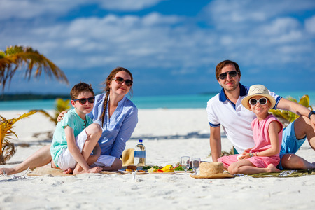 Photo pour Happy beautiful family on a tropical beach having picnic together - image libre de droit