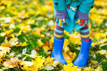 Photo pour Close up of a little girl in colorful clothes and blue boots outdoors at beautiful autumn park - image libre de droit