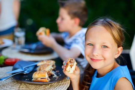Foto de Adorable little girl and her family eating delicious homemade burger outdoors on summer day - Imagen libre de derechos