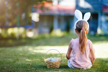 Photo for Back view of a  little girl wearing bunny ears with a basket of colorful Easter eggs outdoors on spring day - Royalty Free Image