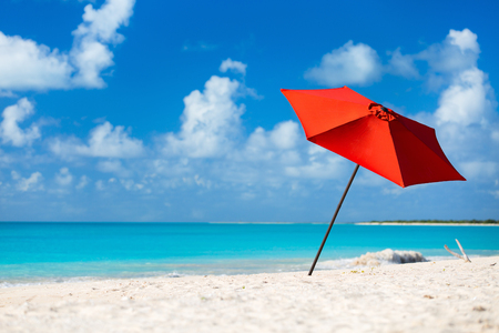 Photo pour Red umbrella on Idyllic tropical beach with white sand, turquoise ocean water and blue sky at deserted island in Caribbean - image libre de droit