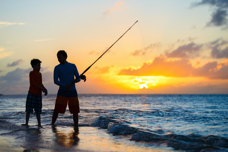 Foto de Father and son fishing together in ocean from beach on sunset - Imagen libre de derechos