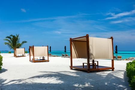 Foto de Day bed cabana on a beautiful tropical beach with a palm tree at Maldives - Imagen libre de derechos