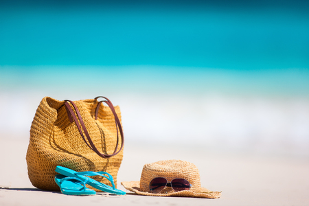 Foto de Straw hat, bag, sun glasses and flip flops on a tropical beach - Imagen libre de derechos