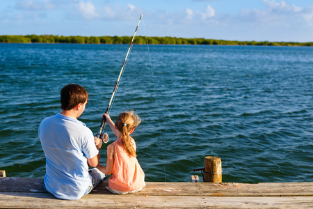 Foto de Family father and daughter fishing together from wooden jetty - Imagen libre de derechos