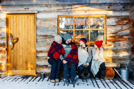 Photo pour Family with kids outdoors on beautiful winter day in front of log cabin vacation house - image libre de droit