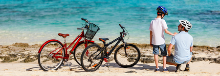 Photo pour Father and kids enjoying sea view at tropical beach with their bikes parked nearby - image libre de droit