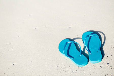 Photo pour Turquoise flip flops on a tropical beach - image libre de droit