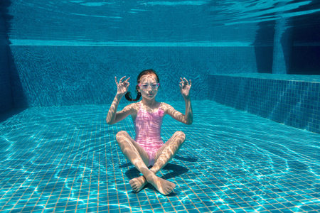 Foto de Underwater photo of playful girl in pool practicing yoga - Imagen libre de derechos