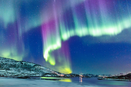 Foto de Incredible Northern lights Aurora Borealis activity above the coast in Norway - Imagen libre de derechos