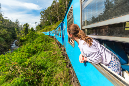 Foto de Young woman enjoying train ride from Ella  to Kandy among tea plantations in the highlands of Sri Lanka - Imagen libre de derechos