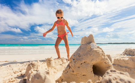 Photo for Little girl at tropical beach making sand castle - Royalty Free Image