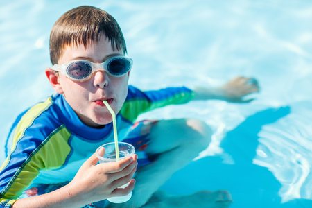 Photo pour Cute boy at all inclusive resort swimming pool sipping cocktail - image libre de droit