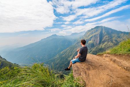 Foto de Young man enjoying breathtaking views over mountains and tea plantations from Little Adams peak in Ella Sri Lanka - Imagen libre de derechos