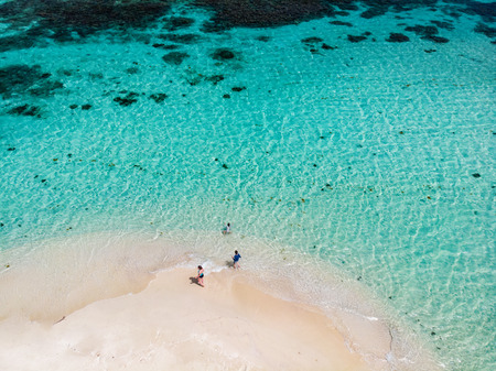 Photo pour Aerial drone view of tiny tropical Mopion island sandbar, turquoise Caribbean sea and a family with kids in St Vincent and Grenadines - image libre de droit