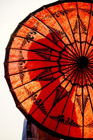 Foto de Young girl silhouette seen through traditional burmese umbrella - Imagen libre de derechos
