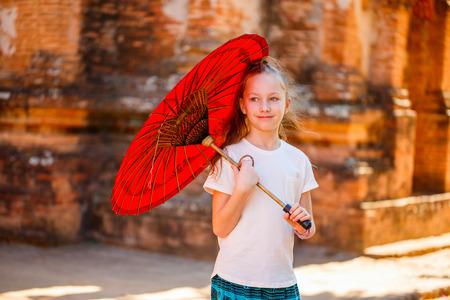 Foto de Young girl with traditional burmese parasol outdoors - Imagen libre de derechos